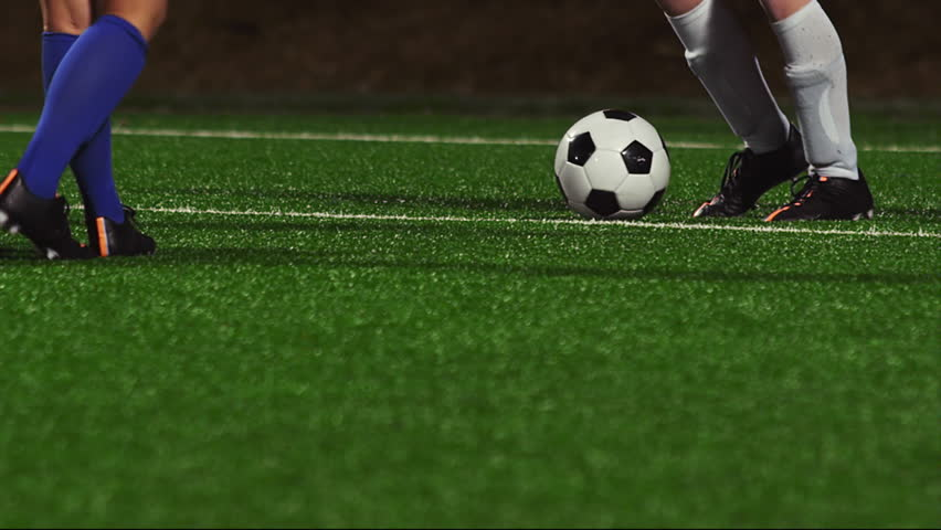 Close up of female soccer players dribbling down the field at night - 4K stock footage clip