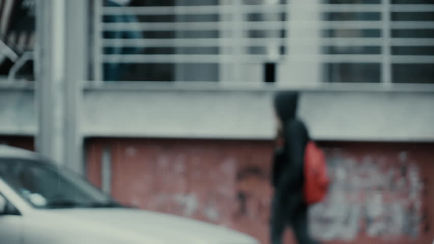 Slow motion hooded teen girl with backpack walking on sidewalk.100fps-25fps conformed slow motion out of focus shot of a teenage girl on the way to school wearing a black hoodie.Rain drops in focus. #12308099