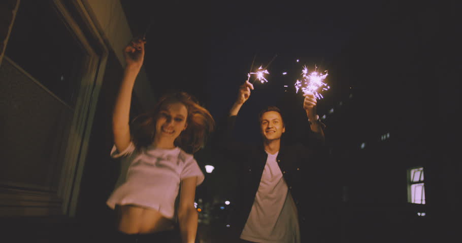 Young couple walking in Slow Motion close together on a city street at night while celebrating with sparklers