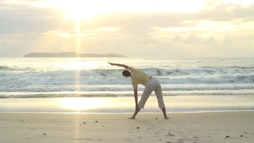 HD 1080i: Young woman doing yoga on the beach at sunrise in Bombinhas - Brazil. Tripod. - HD stock video clip