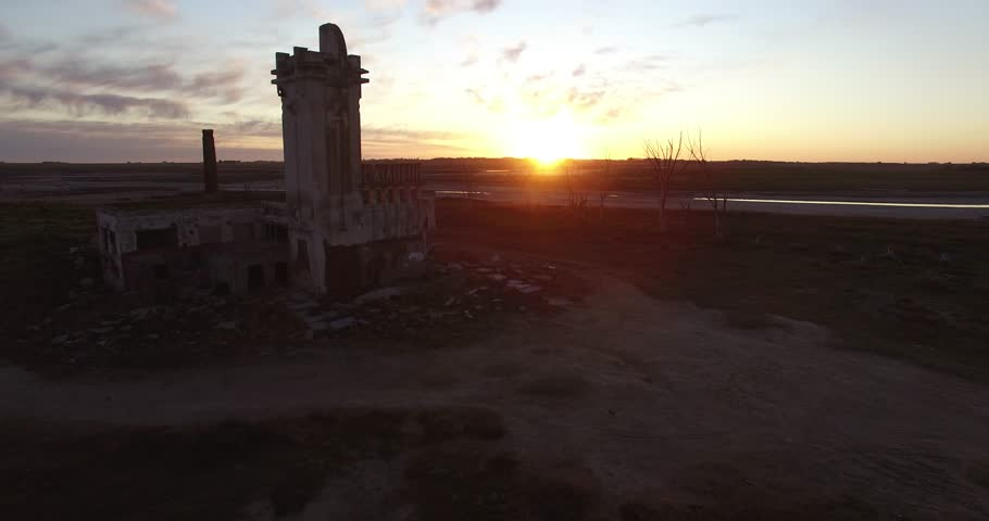Aerial Drone scene of an abandoned Slaughterhouse at sunset, surrounded by dead trees in Epecuen at buenos aires argentina. Horrifying and scary exterior panorama Camera traveling slowly to the front.
