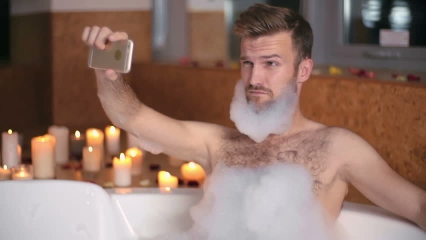Handsome man taking a selfie in the bathtub with soap foam on his beard