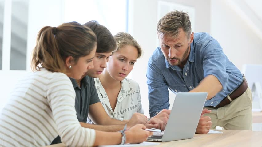 Teacher with group of students working on laptop computer - HD stock footage clip