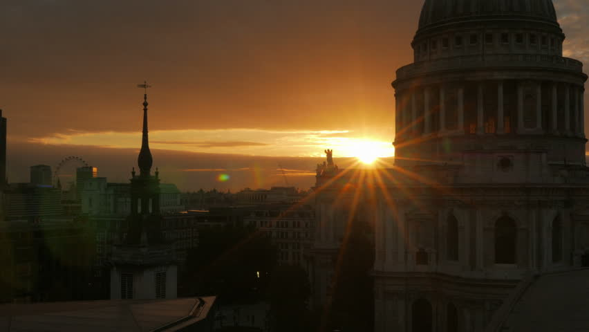 A cinematic, wide angle sunset view by St Paul's Cathedral in the City of London, England, UK. A small lens aperture was used, creating a star burst effect