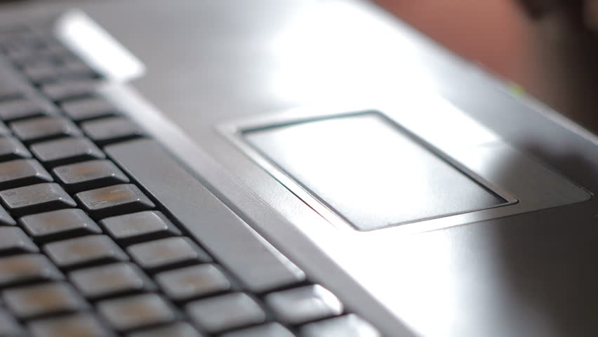 Close up of hand typing and touching touchpad on laptop