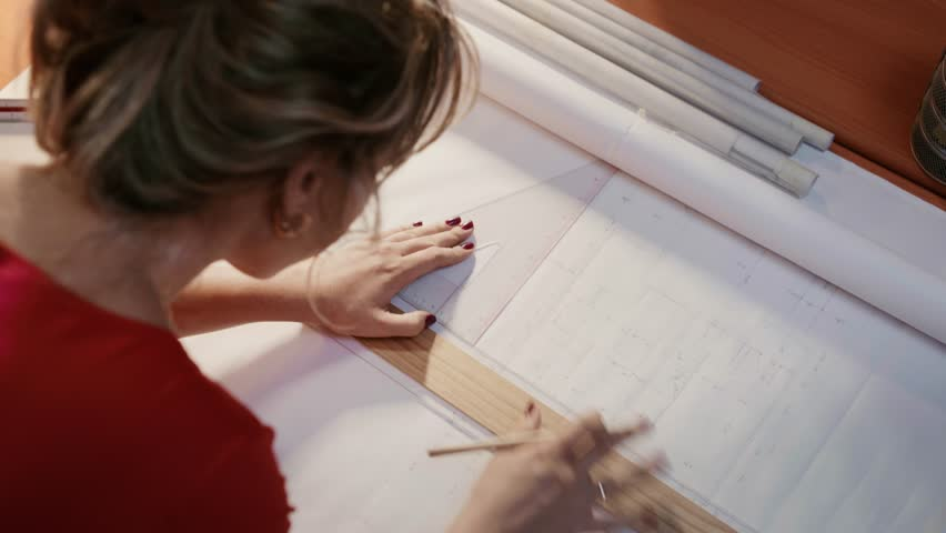 University student of Interior Design doing homework, completing housing project for final exam. The girl draws lines on a blueprint with a rule in her studio. Closeup, dolly shot #12474140