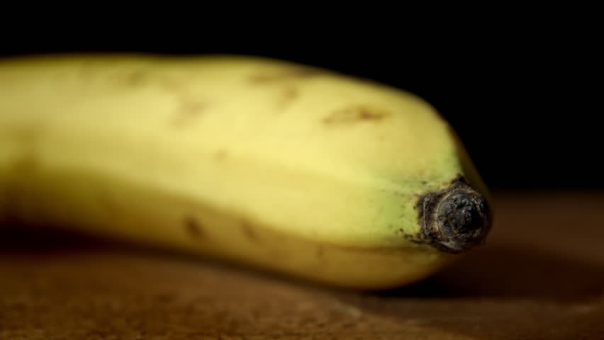Banana close up background HD stock footage. A Banana in close up isolated against a black backdrop with negative space for text overlays. - HD stock footage clip