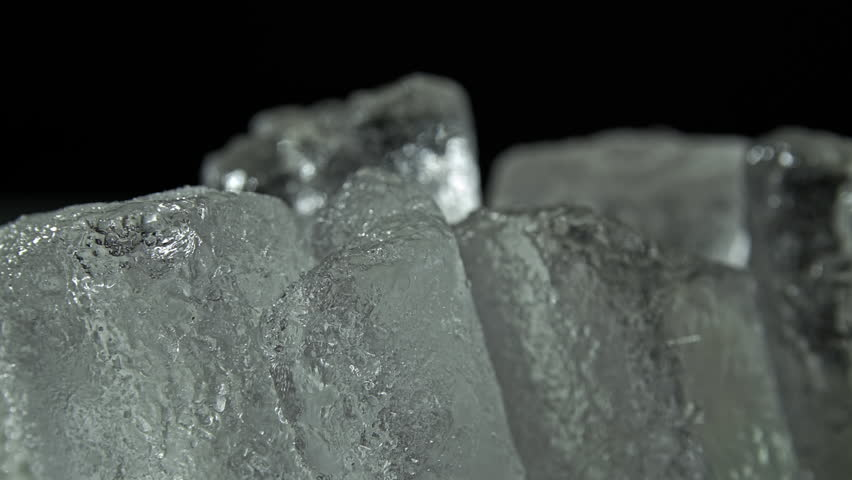 Ice cubes close up HD stock footage. Ice cubes isolated against a black backdrop with a sliding camera move.