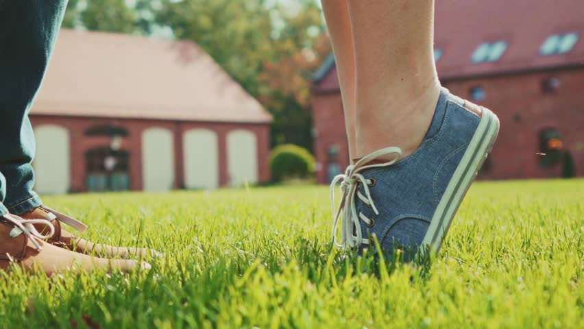 Close up of feet and legs as woman is tip toeing for a kiss. Romantic Couple kissing on a green grass lawn outdoors. Slow Motion 120 fps. Young love concept with lovers kissing. Stylish hipster shoes. #12517547