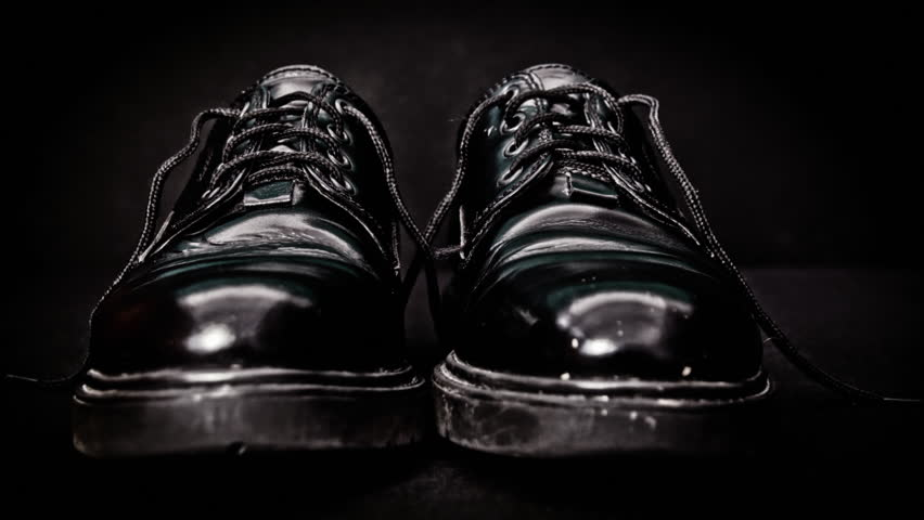 Man's black leather shoe background HD stock footage. Black leather shoe in close up set against a black background with negative space for text overlays.