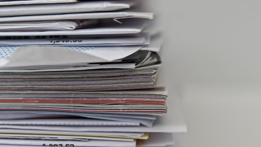 A pile of junk mail HD stock footage. A stack of junk mail with a sliding camera move set against a white backdrop. Negative space for text overlays.