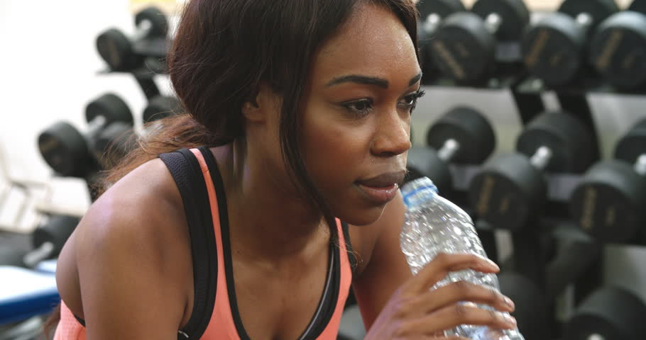 Young African American woman drinking water after exercising