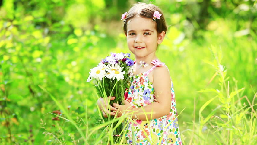 Girl turning with flowers in the  grass  - HD stock video clip