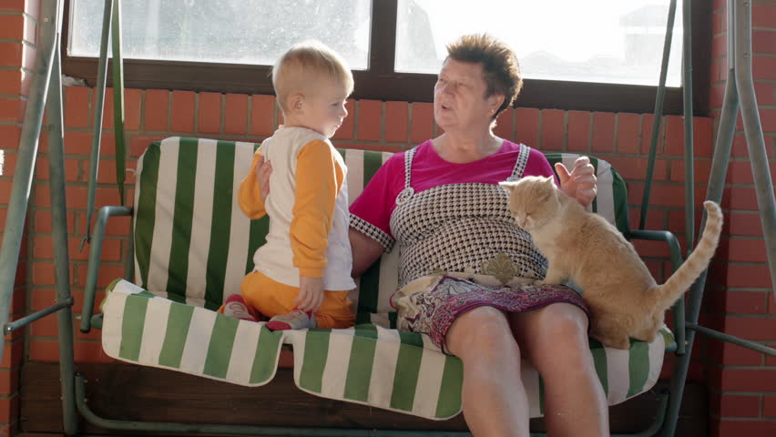 Little boy and his grandmother are sitting on the garden swing bench. Woman is showing to the boy something above. - HD stock footage clip