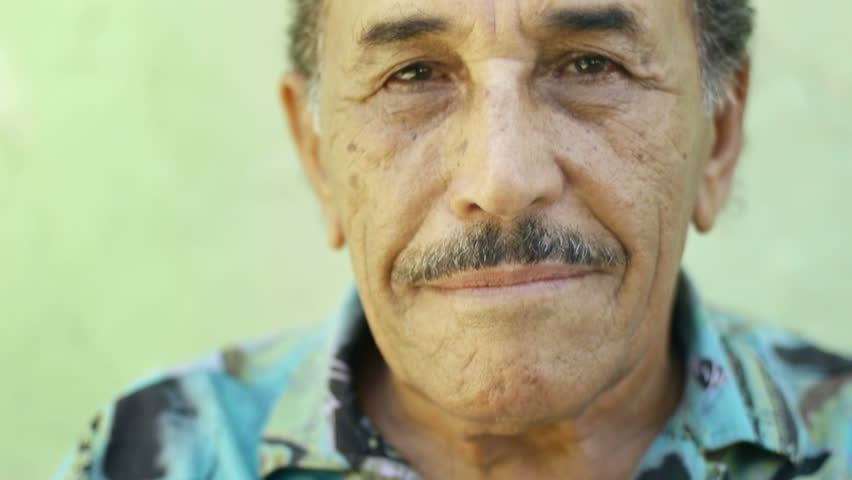 Portrait of senior hispanic man with mustache looking at camera against green wall and smiling. Elderly, old people and feelings - HD stock footage clip