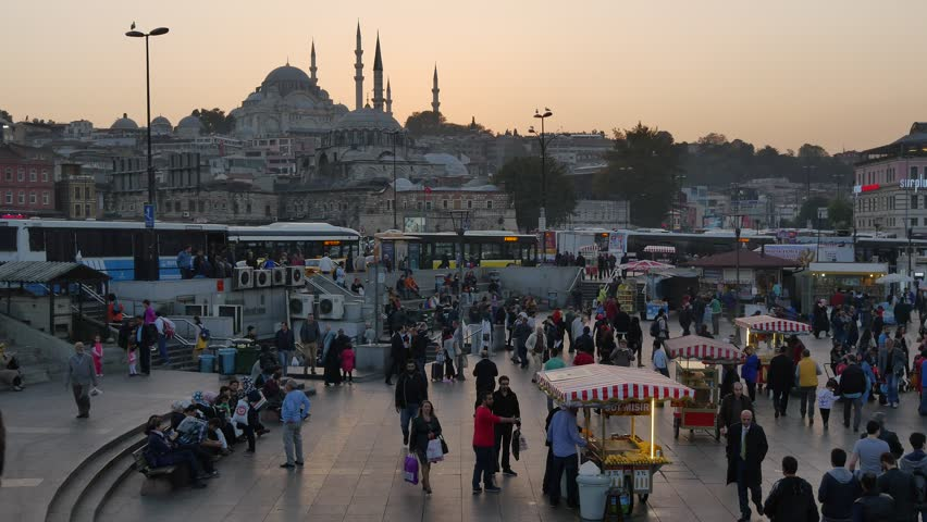 ISTANBUL - SEP 16, 2015: Street seller and the crowd around him in Istanbul. High angle view. Street vendor sells grilled sweet corn, a typical turkish fast food at Eminonu district of Istanbul.