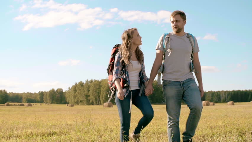 Beautiful couple walking through the meadow holding hands and discussing their direction - HD stock video clip