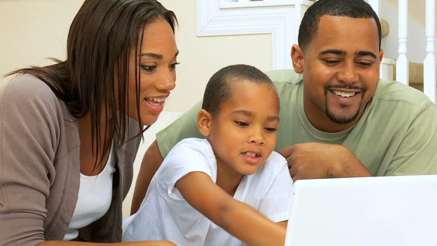 Young african-american boy showing his parents some computer programmes on his laptop
