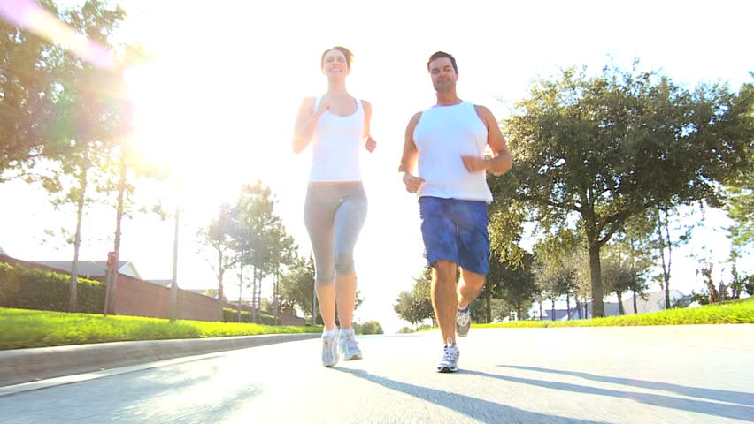 Healthy young couple jogging along suburban road - HD stock footage clip