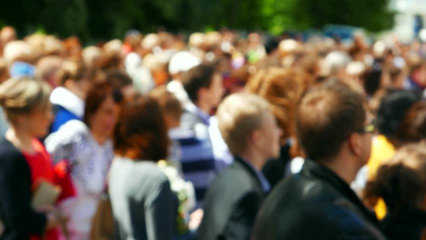 Crowd, meeting a lot of people, men, women and children. Defocus