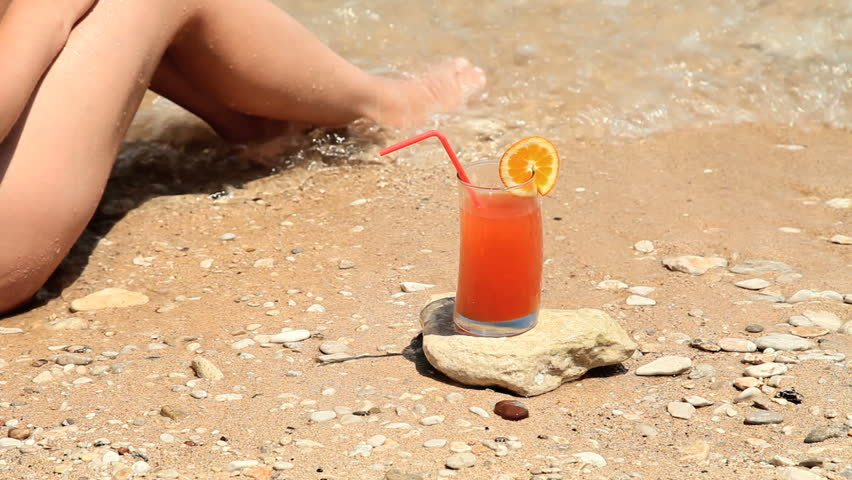 cocktail on the beach with woman taking a sip  - HD stock video clip