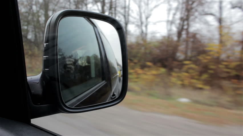 mirror car traveling/side mirror of a car moving on a highway in autumn