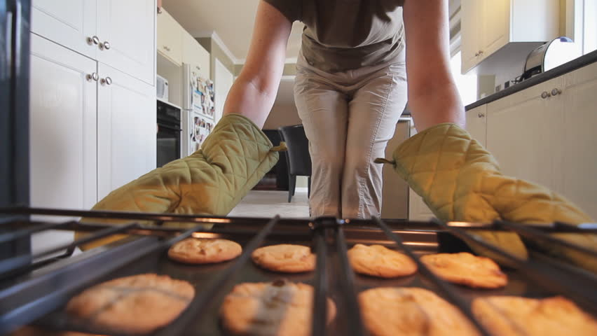 Woman Taking Baked Cookies Out Of An Oven Holding The Hot Baking Sheet With Oven Gloves