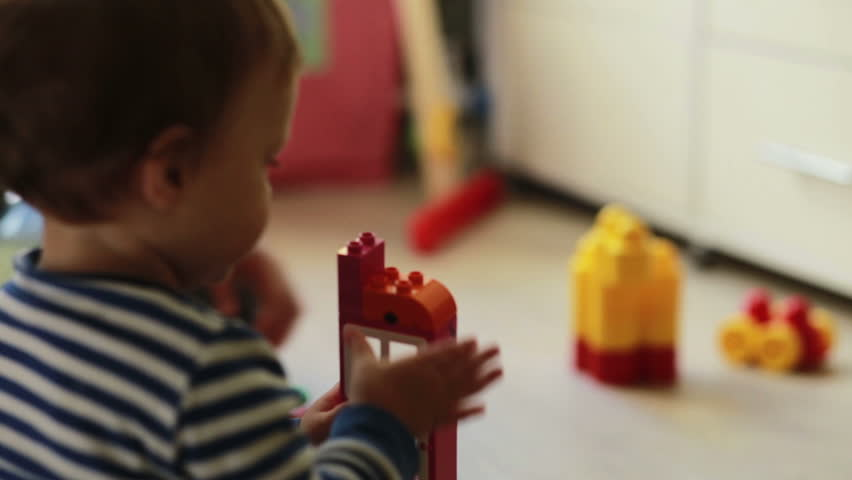 mother playing with her baby boy in bright geometric blocks - HD stock video clip