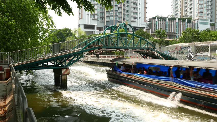 BANGKOK - MARCH 26, 2015: Express boat rush under pedestrian bridge, loudly run towards and pass by. Long and low water craft, popular public transport over Khlong Saen Saep - 4K stock footage clip