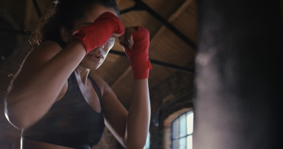 Beautiful Kickboxing woman training punching bag in fitness studio fierce strength fit body kickboxer series | Shutterstock HD Video #12950321