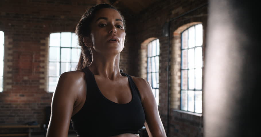 Beautiful Kickboxing woman training punching bag in fitness studio fierce strength fit body kickboxer | Shutterstock HD Video #12950339
