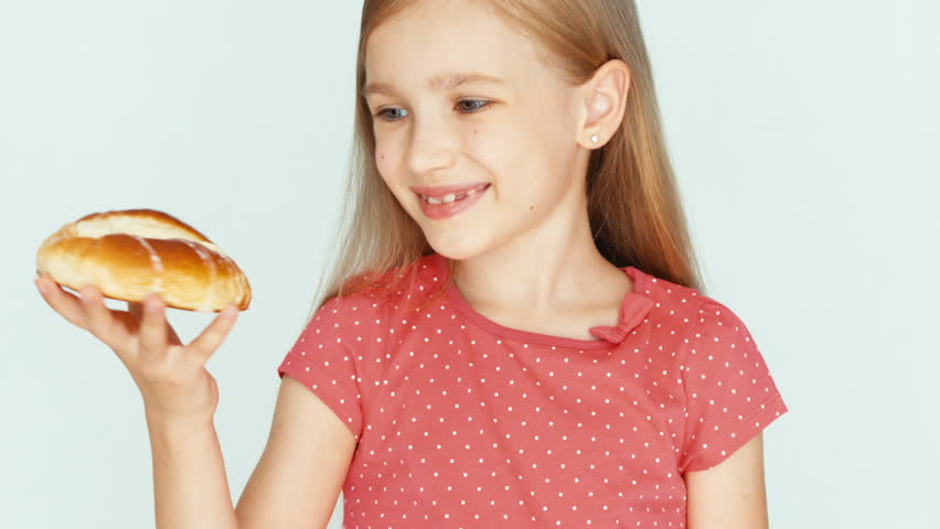 Girl holding a cake with cheese and showing at camera. Child on the white background. Thumb up. Ok. Closeup - HD stock video clip