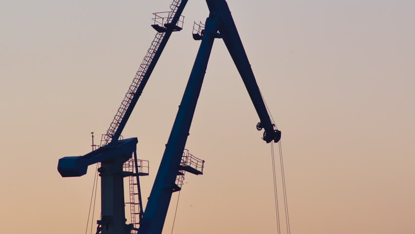 Close up of a silhouetted harbor crane loading freight during golden hour