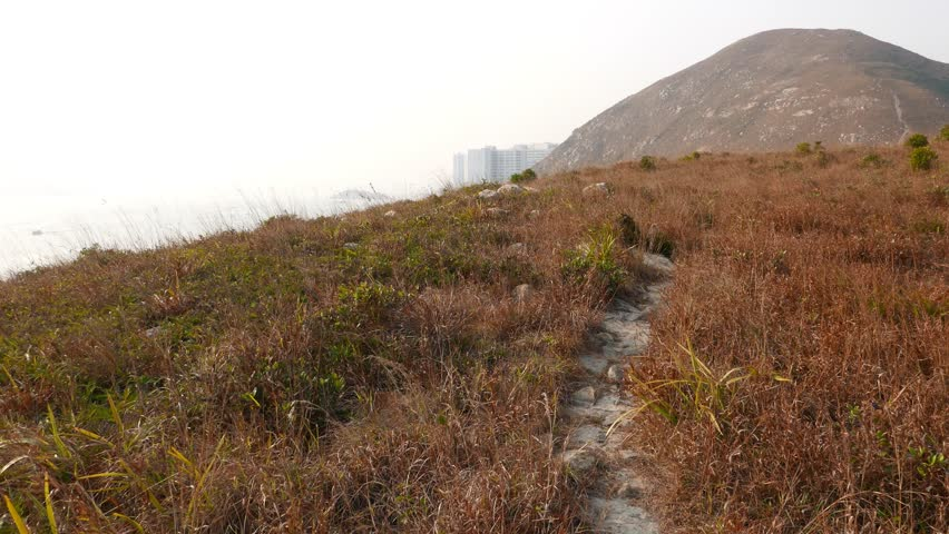 Trodden path over dry grass on top of island, small uninhabited Ap Lei Pai. POV camera move forward, pass winding trampled trail, deserted area around. Long shot, East Lamma channel waters seen far | Shutterstock HD Video #12952688
