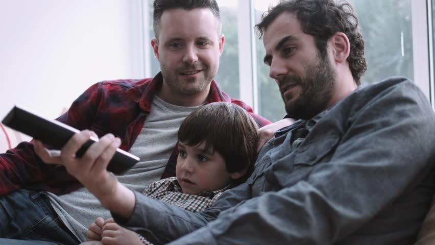 Same sex couple family watching TV on sofa