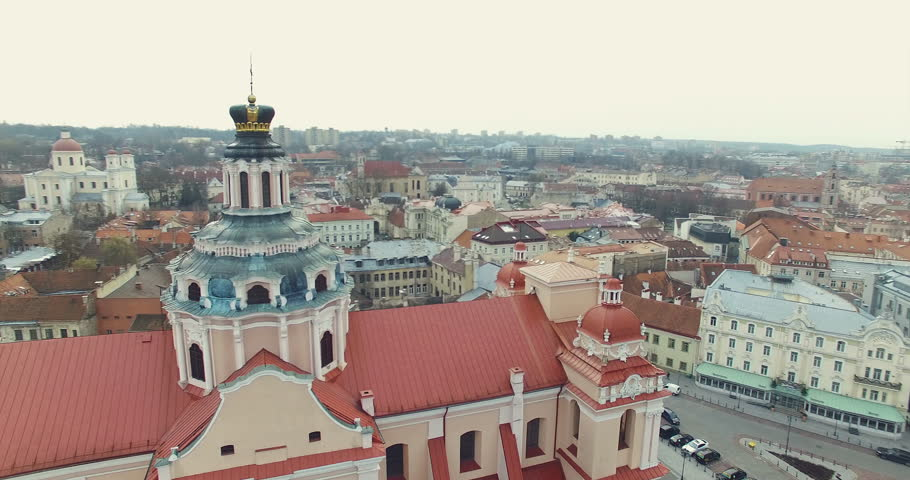 AERIAL. Smooth 360 flight around beautiful Church of St. Casimir in Vilnius old town, Lithuania. Panorama of Vilnius old town