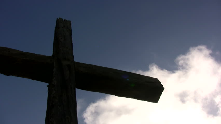 A large cross with white clouds floating behind it. - HD stock video clip