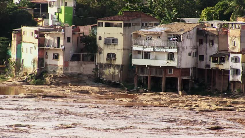 Brown, toxic water from a broken mine dam flows down the river Rio Doce on November 11, 2015 in Governador Valadares.