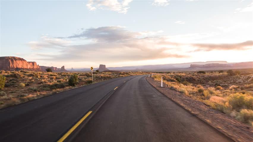 Driving USA: Sunset sunrise point of view shot along empty desert highway through Monument Valley, Arizona Utah