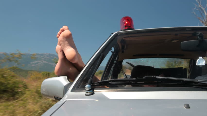 Woman hanging out legs from window riding  police car with siren - HD stock footage clip
