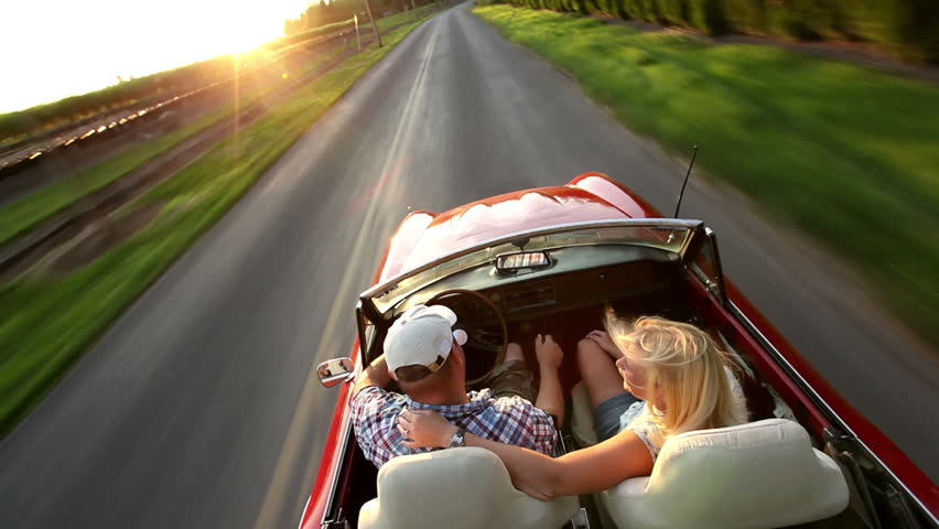 Cinemagraph - Couple in convertible car driving. Looping Motion Photo.