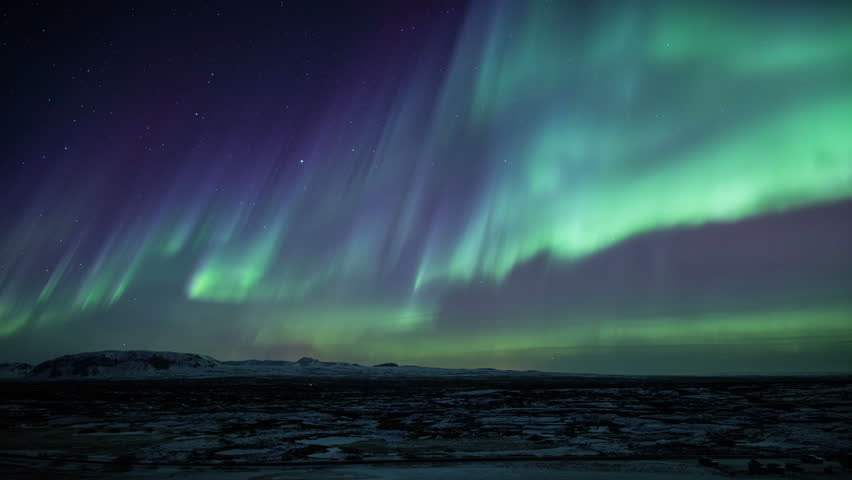 Strong bright Aurora Borealis snow covered lava field mountains Thingvellir Iceland realistic movement 4k