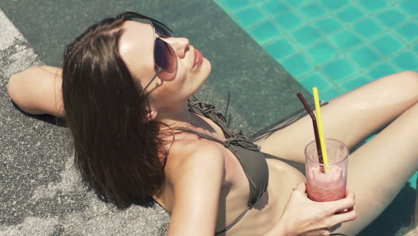 Pretty woman relaxing and drinking cocktail by pool, slow motion 240fps