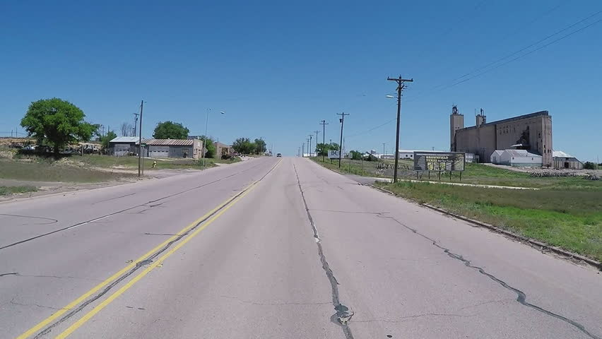 BROWNFIELD, TX/USA - July 11, 2015: Point of view vehicle driving shot of driving through small town. A traveler's viewpoint of rural country businesses and companies in a farming and oil town. - HD stock video clip