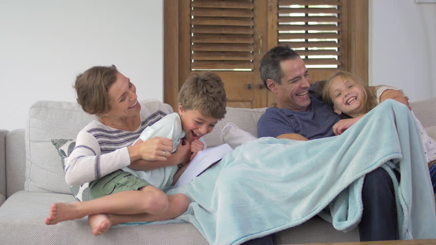 Family tickle fight on couch at home with kids jumping to surprise parents