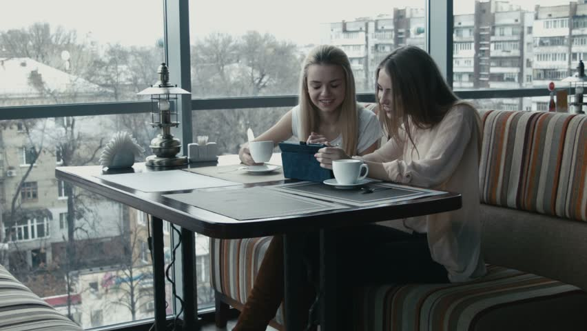 The girl shows to the girlfriend something on the touchpad in cafe | Shutterstock HD Video #13189217