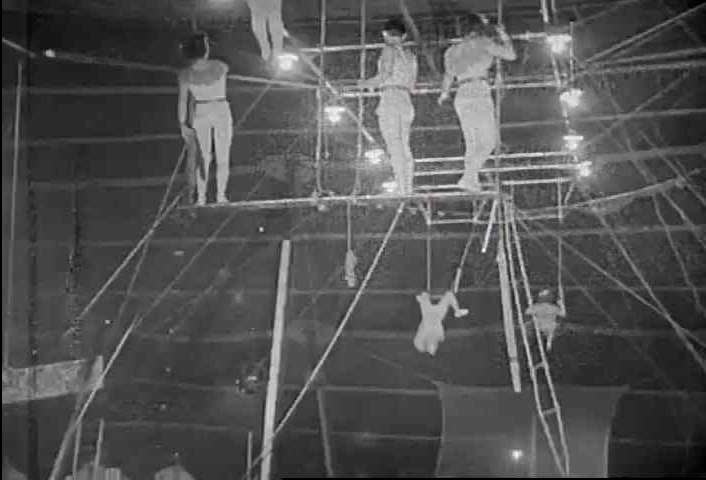 CIRCA 1940s - Acrobats at the American circus swing on the high aerial bars in 1942.