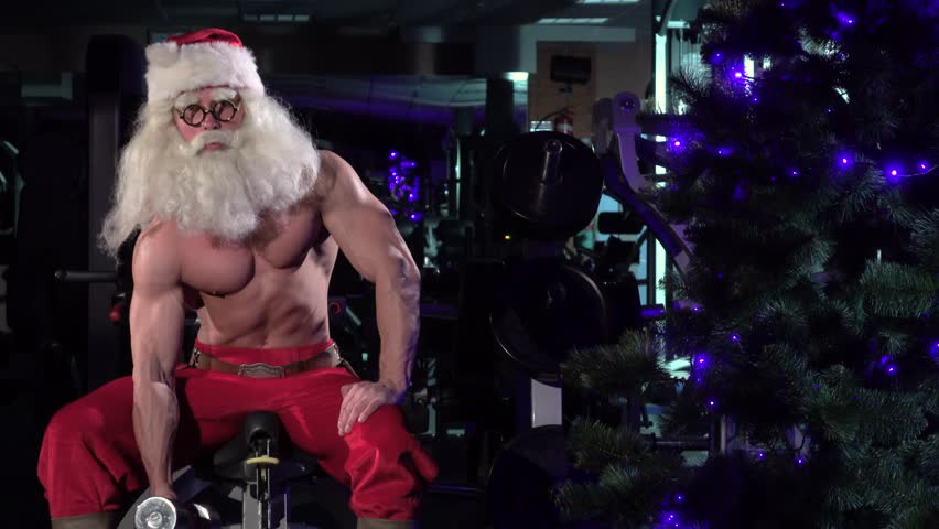 Santa in a gym training biceps near the Christmas tree