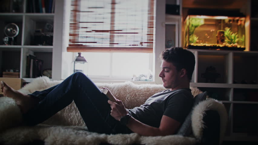 Cinemagraph (Photo-Motion) of a Young Relax Adult Reading a Book on the Couch | Shutterstock HD Video #13269749