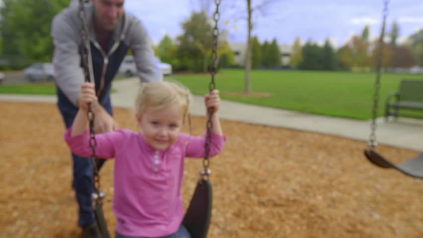 Father pushes his daughter on a swing as she smiles for the camera | Shutterstock HD Video #13307765